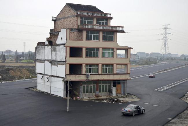 """Một ngôi làng ở Chiết Giang bắt đầu di dời để phục vụ việc làm đường cao tốc. Tuy nhiên, đôi vợ chồng già kiên quyết không chuyển nhà. Giới bất động sản đặt tên cho những ngôi nhà kiểu này là """"nhà đinh"""". Ảnh: China Daily Infor."""