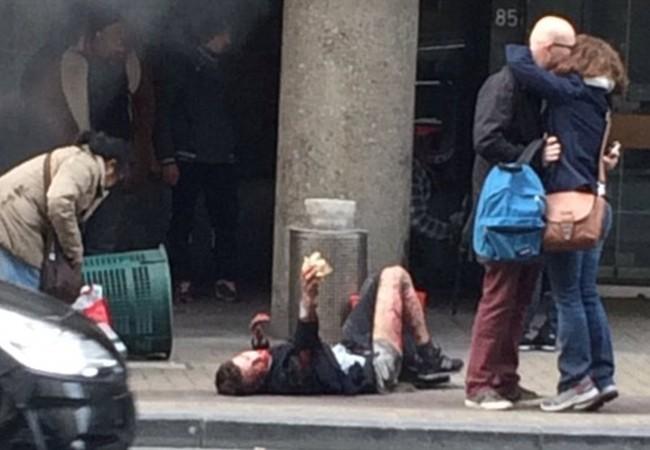 Người đàn ông bị thương đang nằm trên vỉa hè cạnh 2 người vui mừng nhẹ nhõm vì sống sót sau vụ đánh bom tại ga tàu điện ngầm ở Maelbeek