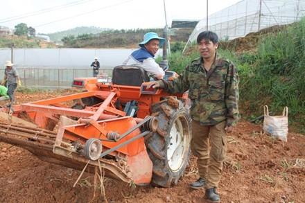 Anh Phạm Minh Thành đứng kế máy đào khoai tây đa năng tự tay anh sáng chế.