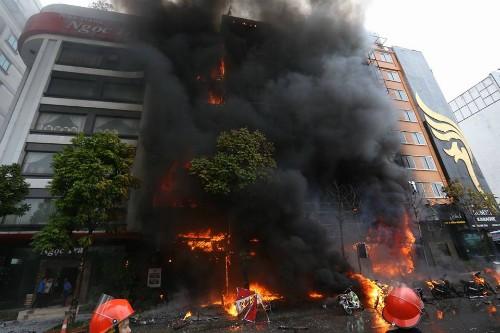 Ngọn lửa bốc cao thiêu rụi mặt tiền nhiều nhà cao tầng. Ảnh: Bá Đô.