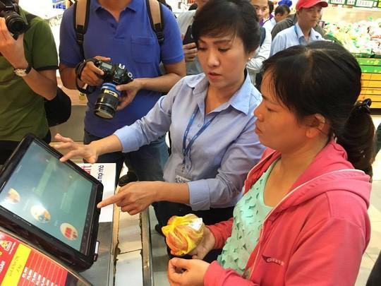 Nhân viên Co.opmart Foodcosa Quang Trung (Gò Vấp) hướng dẫn khách hàng cách kiểm tra nguồn gốc thịt heo bằng máy soi đặt tại siêu thị