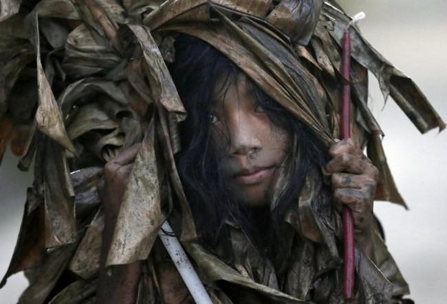 Một bé gái quàng lá chuối khô và trét bùn lên cơ thể trong lúc diễn ra lễ hội người bùn - Ảnh: AP