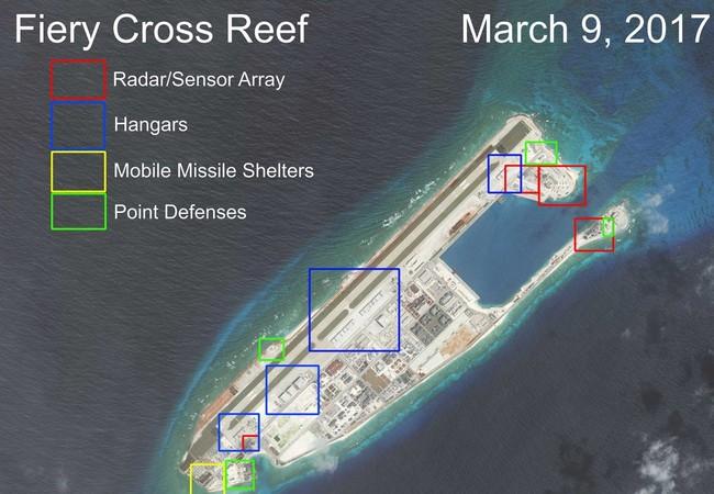 Cận cảnh Đá Chữ Thập đã bị Trung Quốc bồi lấp, xây đảo nhân tạo trái phép với đường băng và các công trình quân sự tại quần đảo Trường Sa. Khu vực màu đỏ là nơi bố trí các hệ thống radar. Khu vực màu xanh dương là nhà chứa máy bay. Khu màu vàng xây dựng c