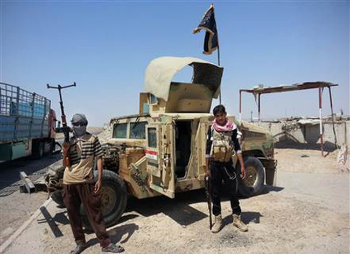 Phiến quân IS đứng cạnh một xe Humvee chiếm được của Iraq tháng 6/2014. Ảnh: AP