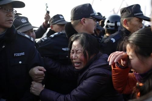 Thân nhân hành khách của tàu Ngôi sao phương Đông định phá hàng rào cảnh sát dọc sông Trường Giang. Ảnh: Reuters