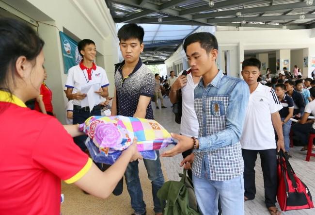 Thí sinh tỉnh Bình Thuận được sinh viên tình nguyện phát mền gối để vào KTX nghỉ miễn phí tại cụm thi Trường ĐH Tôn Đức Thắng sáng 29-6 - Ảnh: Như Hùng