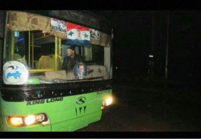 Xe buýt màu xanh của chính quyền Syria chở chiến binh thánh chiến lên đường về Idlib