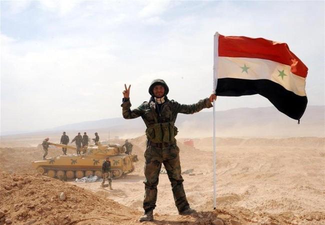 Binh sĩ Syria cùng lá cờ trên sa mạc Palmyra (ảnh minh họa)