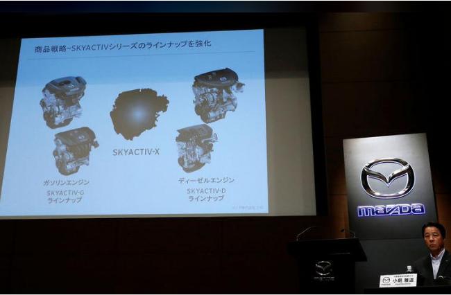 Chủ tịch hãng Mazda Masamichi Kogai bên cạnh màn hình giới thiệu động cơ mới tại cuộc họp báo ở Tokyo ngày 8/8. Ảnh Reuters