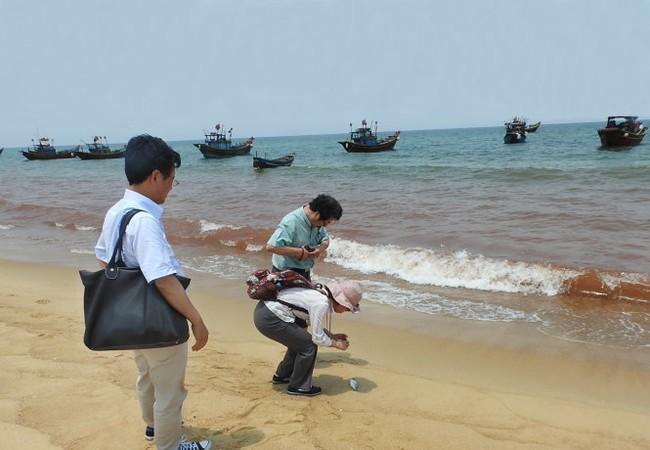 Cơ quan chức năng lấy mẫu nước tại vùng biển có màu đỏ để xét nghiệm - Ảnh: Nguyệt Anh