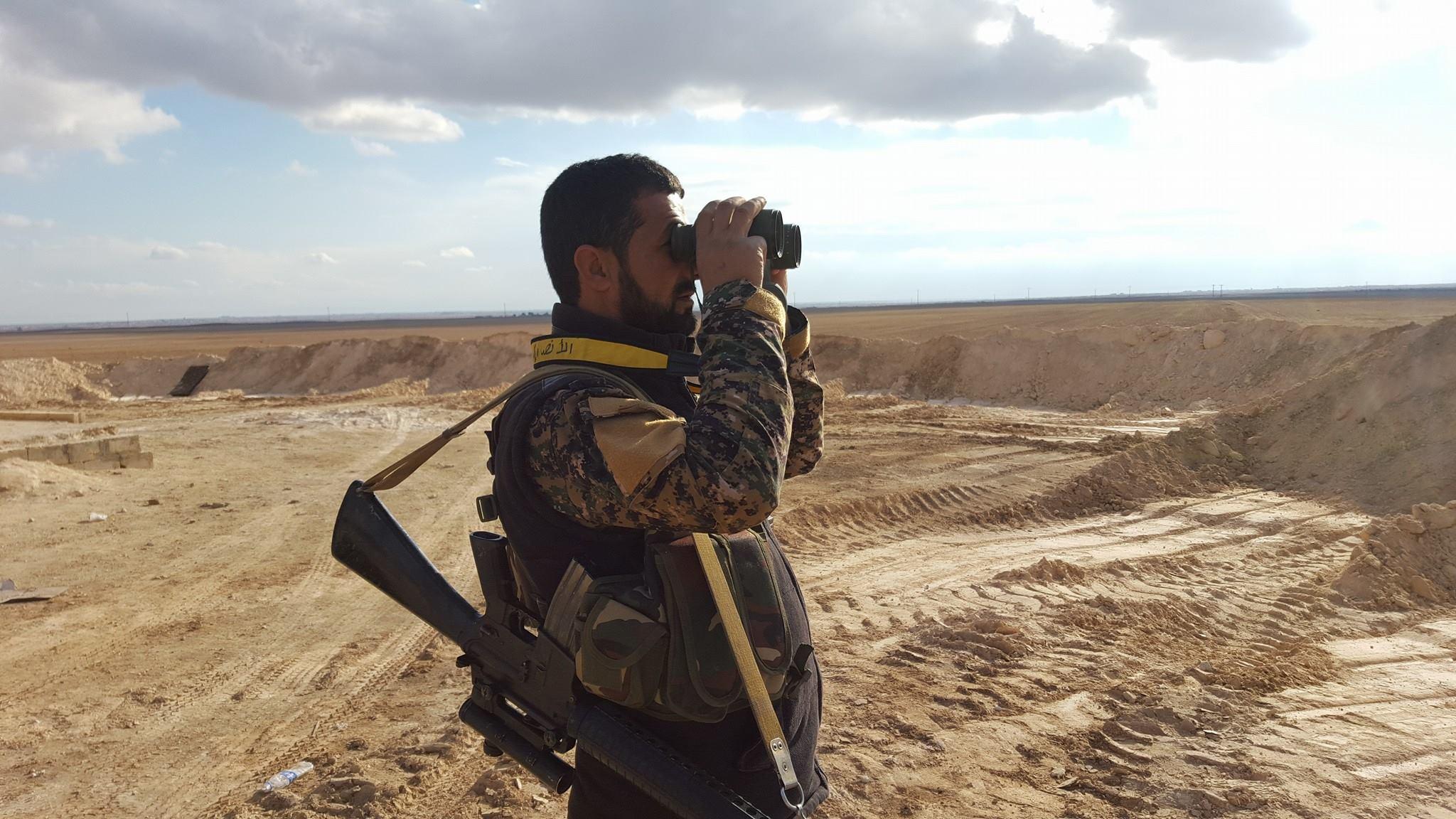 Một sĩ quan quân đội Syria đang quan sát chiến trường tỉnh Homs, Hama